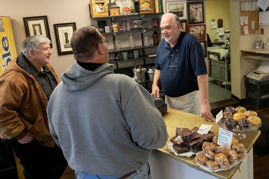 Paul Dominello, owner of Paul's Deli and Catering, center, helps regular customers Billy Stanley, of Meriden, left, and Chris Macinvale, of Middlefield, second from left, inside the store   in Meriden on Monday, Dec. 2. The business, established in 1979, is celebrating 40 years.Dave Zajac, Record-Journal