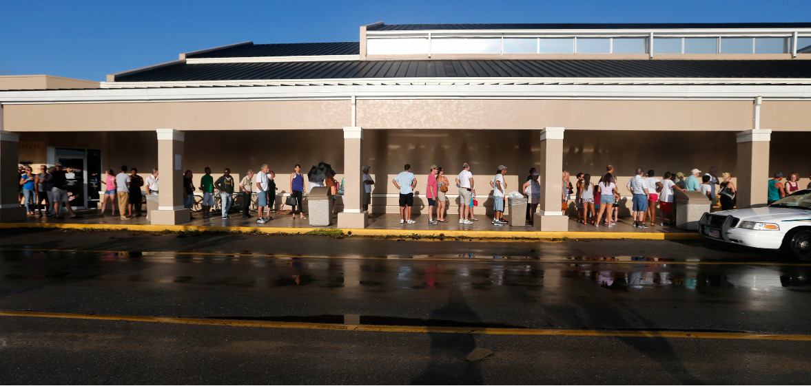 People line up for the announced opening of a Publix grocery store, the first food chain to re-open in Naples, in the aftermath of Hurricane Irma, which passed through Sunday, in Naples, Fla., Tuesday, Sept. 12, 2017. The store could not open its doors on time because they were trying to get the cash registers online. (AP Photo/Gerald Herbert)