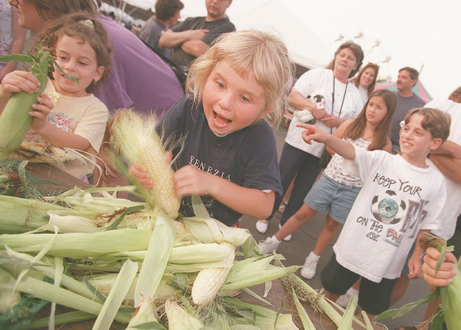 RJ file photo - Isabella Kowalski, 8, of Wallingford, feverishly rips the husks off an ear of corn during a corn-shucking contest at Our Lady of Fatima Church Carnival in Wallingford, Aug. 4, 1998. Isabella shucked seven ears in 60 seconds.