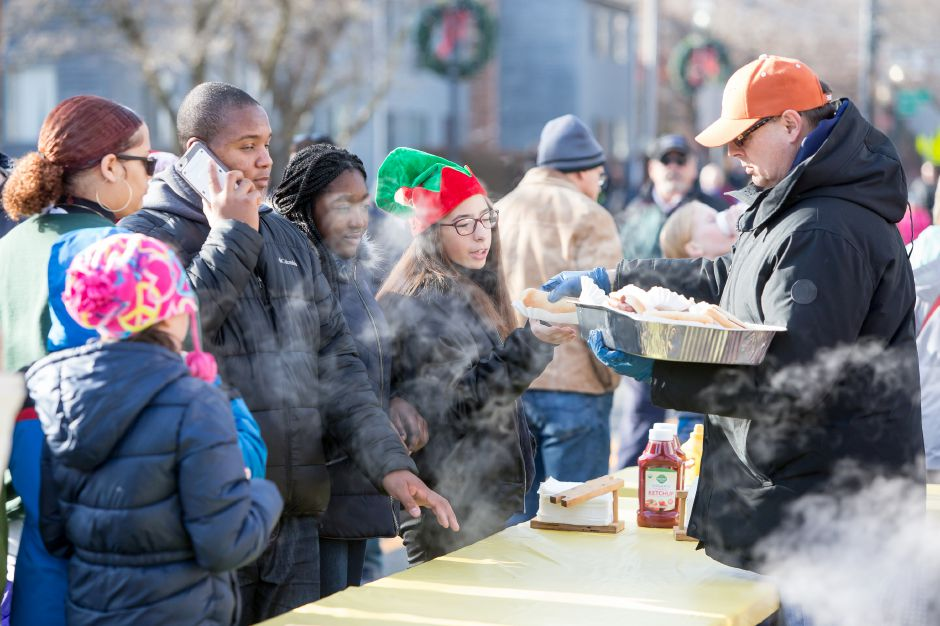 Roger Crochetiere serves a hotdog to Teagan Burns 14 of South Meriden Saturday during Christmas in the Village on Main Street in South Meriden December 1, 2018 | Justin Weekes / Special to the Record-Journal
