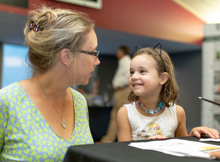 Mariella Ponte, 5, smiles while filling out her passport to  Wallingford schools' STEM challenge. The event Monday at the Oakdale Theatre gave children math games and engineering tasks to figure out with their families.  Devin Leith-Yessian, Record-Journal