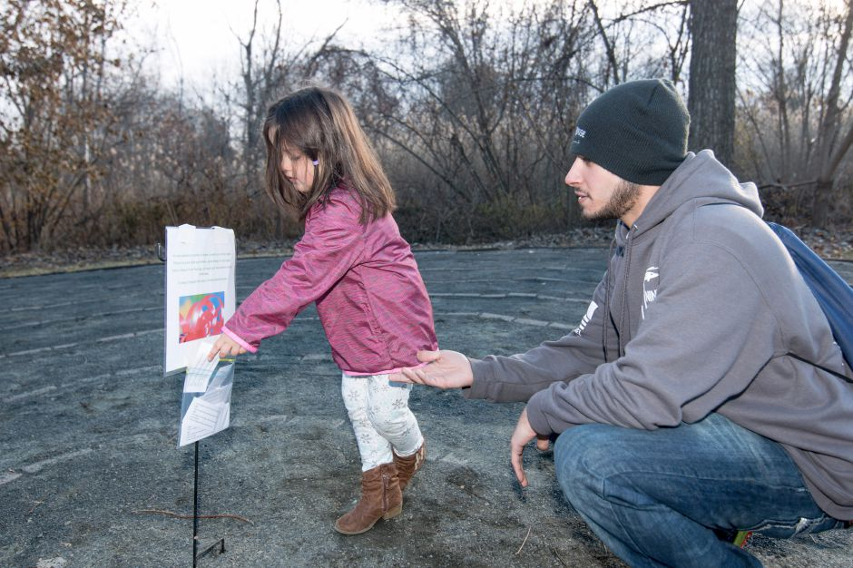 Ellena Burkowski, 4, and John Infante, both from Wallingford, take one of the hints scattered along the Quinnipiac Linear Trail for the Holiday Celebration on the Linear Trail scavanger hunt at Lakeside Park on Sunday.
