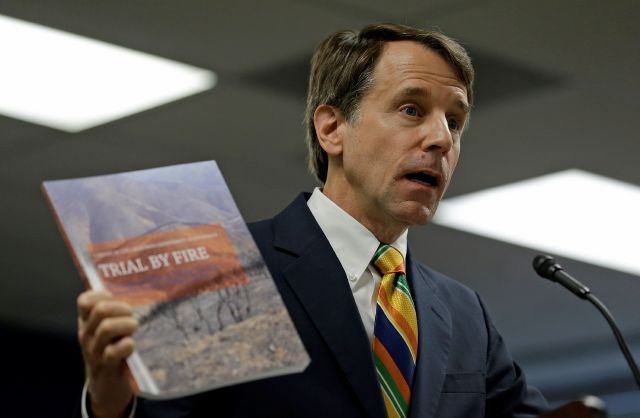 California Insurance Commissioner Dave Jones holds up a copy of a report during a news conference about the costs of recent wildfires Thursday, Sept. 6, 2018, in San Francisco. Jones released the first data on the total insurance claims reported for residential and commercial losses following the Carr and Mendocino Complex wildfires. Commissioner Jones also released updated data for the 2017 California wildfires and 2018 mudslides. (AP Photo/Eric Risberg)