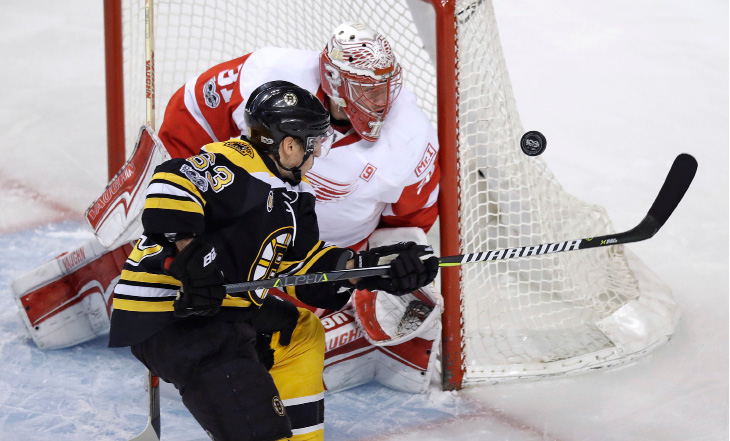 Boston Bruins left wing Brad Marchand (63) tries to tip the puck down against Detroit Red Wings goalie Jared Coreau (31) during the first period of an NHL hockey game in Boston, Wednesday, March 8, 2017. (AP Photo/Charles Krupa)