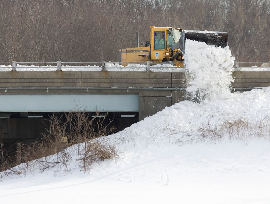 A Connecticut Department of Transportation tractor pushes snow over the rail of the I-84 overpass of Route 10 in Southington, Friday afternoon, Jan. 14, 2011. DOT crews were busy cleaner snow banks from highways after Wednesdays massive snow storm. (Christopher Zajac/Record-Journal)