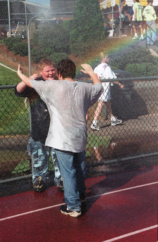 RJ file photo - Seth Tucker, left, and Chris Wills cool off in a water spray set up at the north end of the Platt track for Relay for Life Fri., May 21, 1999 as a rainbow forms over them.