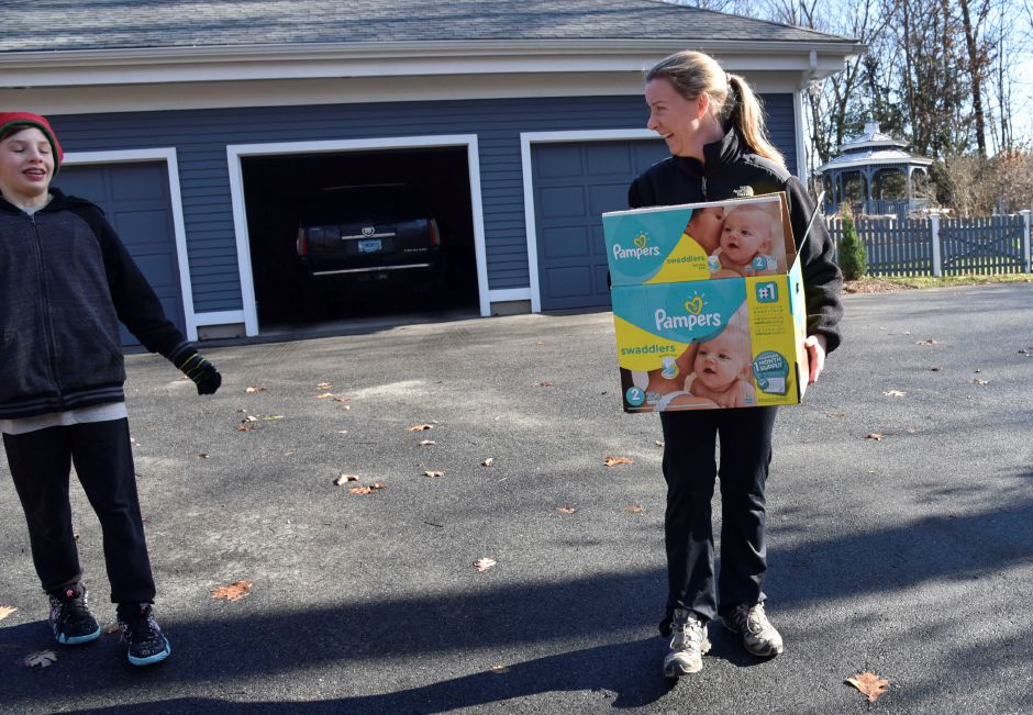 Durham resident Erin Macintosh helps carry her donations to a pickup car during the 13th annual Community Round-up in Durham and Middlefield on Saturday, Dec. 1, 2018. The event collected more than 13,000 food items and about $3,500 to go to Durham and Middlefield Social Services, and Amazing Grace in Middletown. | Bailey Wright, Record-Journal