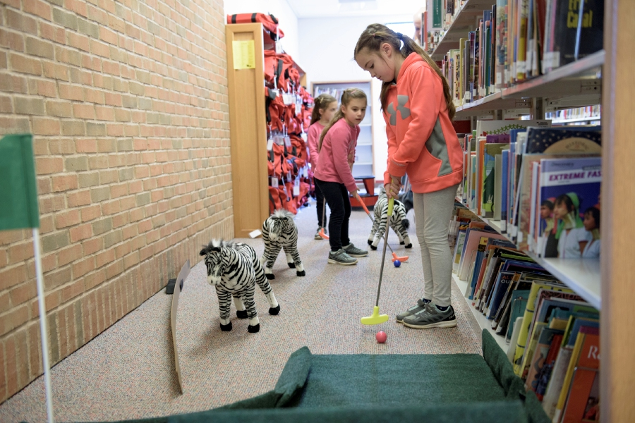 From left, Sophie Nardi-Nemith, 6, Charlotte Nardi-Nemith, 6, and Emma Nardi-Nemith, 7, of Wallingford, play the course.