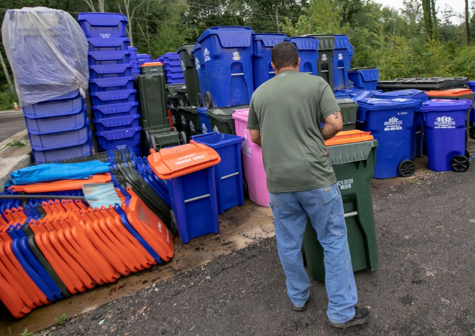 Jack Perry, co-owner of HQ Dumpsters & Recycling, replaces a trash container at the business in Southington, Tuesday, Sept. 11, 2018. Residents could see a potential increase in trash pickup fees due to new charges from the facility contracted to collect recyclables from the towns' commercial haulers. Dave Zajac, Record-Journal