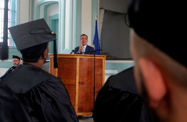 Connecticut Gov. Dannel P. Malloy speaks during graduation ceremonies on Wednesday. Aug. 1, 2018 inside the Cheshire Correctional Institution in Cheshire, Conn. Eighteen inmates received associate degrees from Middlesex Community college as part of a program with Wesleyan University
