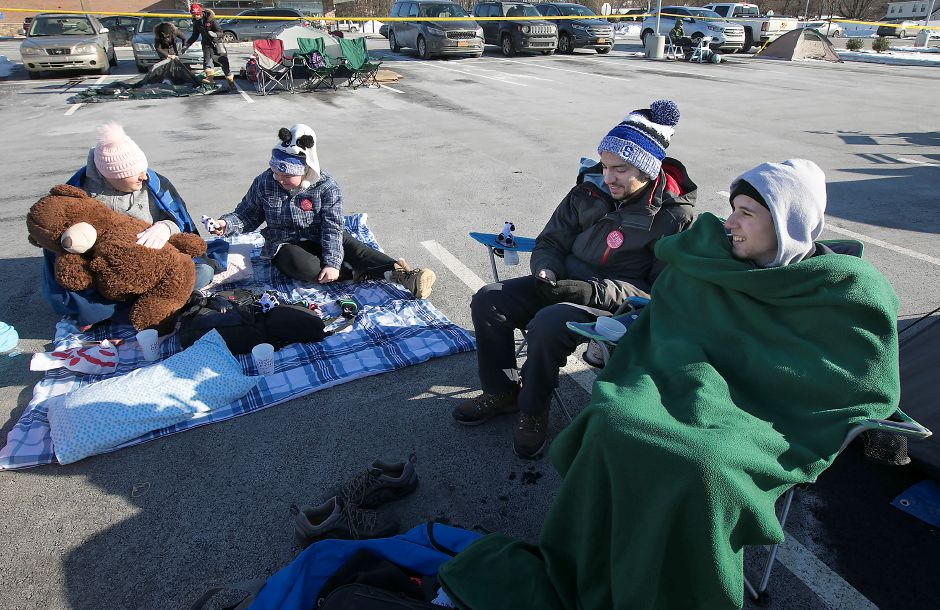 Left to right, John Thompson, Amanda Thompson, Nick Rappi, and Matteo Gaudio, all of Southington, pass the time trying to stay warm while waiting for the opening of the new Chick-fil-A on Queen Street in Southington, Wednesday, Jan. 10, 2018. Campers waiting until the doors officially open Thursday morning win free meals for a year. | Dave Zajac, Record-Journal