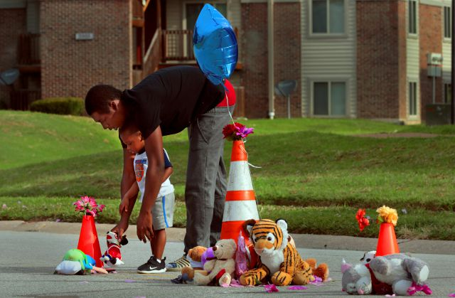 "Canfield Green Apartments resident Marcus Hill helps his son Messiah Hill, 2, place a stuffed animal at a newly rebuilt memorial to Michael Brown, Jr. on Thursday, Aug. 8, 2019 in Ferguson, Mo. The site is where Brown was shot and killed by a Ferguson police officer on Aug. 9, 2014. ""We see his father all the time,"" said Hill of Michael Brown, Sr. ""I"