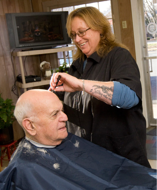 Barber Maria Mazzacane Perez, gives a trim to long time patron Marvin Cohen, of Hamden, at Cheshire Barber Shop in Cheshire, Friday, December 9, 2016. Cohen has been getting his hair cut at the business for nearly 60 years.   | Dave Zajac, Record-Journal