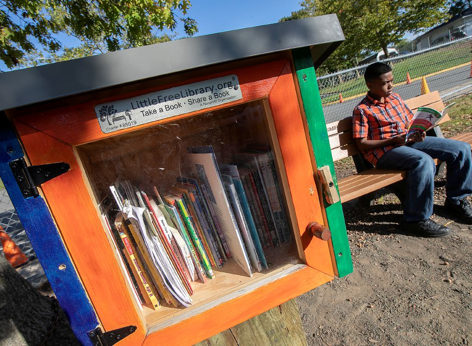 Jason Hayes II, 10, of Meriden, reads a Spider-Man book from the Little Free Library, left, he helped establish at Casimir Pulaski Elementary School in Meriden, Wed., Sept. 18, 2019. Dave Zajac, Record-Journal