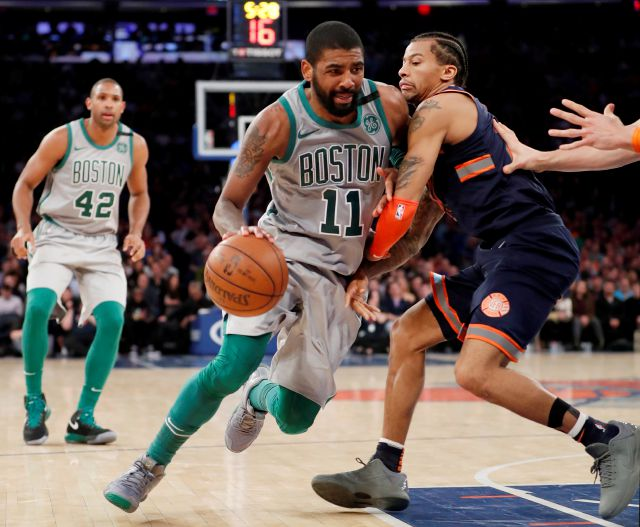 Boston Celtics guard Kyrie Irving (11) drives past New York Knicks guard Trey Burke, right, during the second half of an NBA basketball game in New York, Saturday, Feb. 24, 2018. Irving had 31 points to lead the Celtics in a 121-112 victory. Celtics forward Al Horford is at left. (AP Photo/Kathy Willens)
