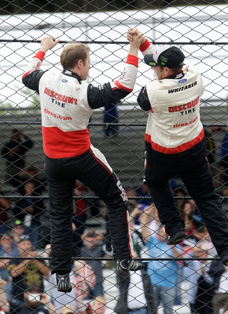 NASCAR Cup Series driver Brad Keselowski (2) celebrates by climbing the fence after winning the NASCAR Brickyard 400 auto race at Indianapolis Motor Speedway, in Indianapolis Monday, Sept. 10, 2018. (AP Photo/AJ Mast)