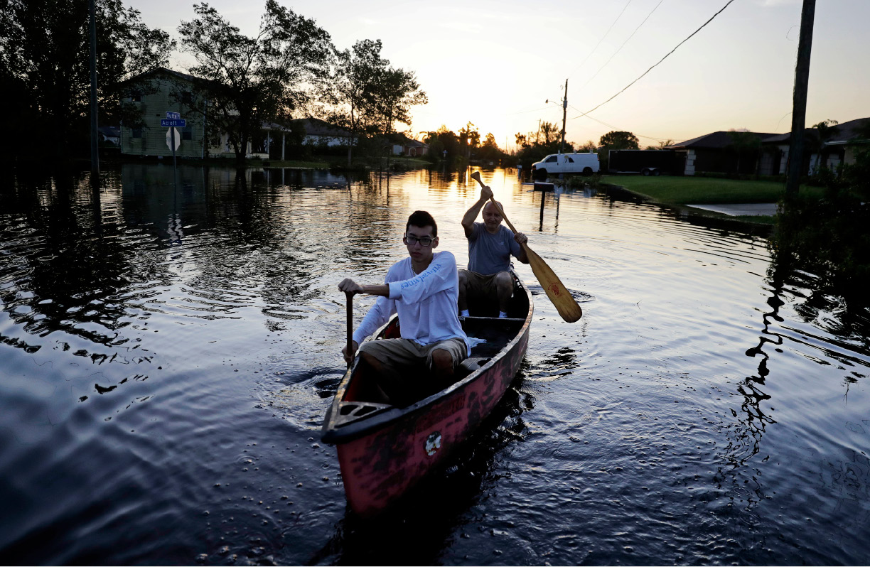 Pierre Ghantos, rear, and his son Nathan paddle though their flooded neighborhood in the aftermath of Hurricane Irma in Fort Myers, Fla., Tuesday, Sept. 12, 2017. (AP Photo/David Goldman)
