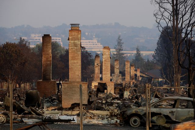 FILE - In this Oct. 13, 2017 file photo, a row of chimneys stand in a neighborhood devastated by a wildfire near Santa Rosa, Calif. Insurance Commissioner Dave Jones is releasing Thursday, Sept. 6, 2018, the first data on the total insurance claims reported for residential and commercial losses following the Carr and Mendocino Complex wildfires. Commissioner Jones will also release updated data for the 2017 California wildfires and 2018 mudslides. (AP Photo/Jae C. Hong, File)