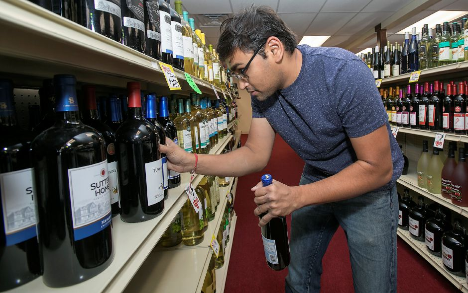 Akash Patel, manager of West Side Wine and Spirits on Hope Hill Road in Wallingford, stocks shelves with wine, Wednesday, Sept. 13, 2017. The store recently opened at the corner of Hope Hill Road and Highland Avenue after about a year of renovations. The owners will also be opening Suburban Market grocery store next door in early 2018. | Dave Zajac, Record-Journal