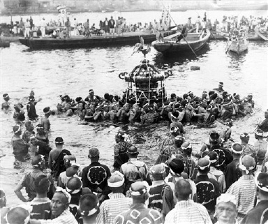 View of the ancient mid-Summer festival of the Tsukuda Shrine showing fisherman carrying the Mikoshi across the river to Tokyo