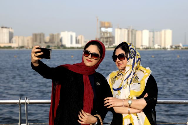 In this Saturday, July 7, 2019, photo, Iranians take selfie around of the Persian Gulf Martyrs lake, west of Tehran, Iran. A few daring women in Iran