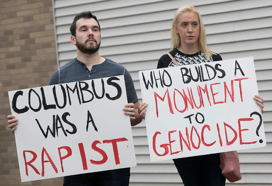James and Stephanie DeMarco, of New Britain, protest during the dedicaton and unveiling of a Christopher Columbus monument at Southington
