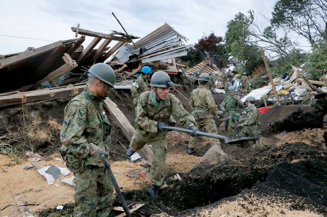Japan Ground Self-Defense Force personnel search for missing persons at the site of a landslide triggered by a powerful earthquake in Atsuma town, Hokkaido, northern Japan, Friday, Sept. 7, 2018. A powerful earthquake Thursday on Japan