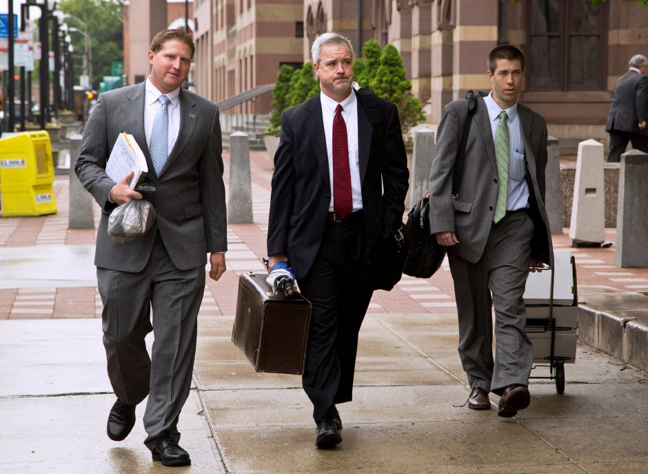 Officer Evan Cossette, left, and his attornies, Raymond Hassett, center, and Jeffrey McDonald, right, arrive at the U.S. Courthouse in New Haven, Conn. Wednesday morning for the second day of his trial on charges of obstruction of justice and deprivation of rights, May 29, 2013. Cossette, a Meriden, Conn. police officer, is accused of using excessive force on a prisoner, Pedro Temich, and falsifying the report to cover up the abuse. (Christopher Zajac / Record-Journal)