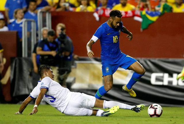 Brazil forward Neymar, right, dribbles over El Salvador defender Roberto Dominguez in the second half of a soccer match, Tuesday, Sept. 11, 2018, in Landover, Md. Brazil won 5-0. (AP Photo/Patrick Semansky)