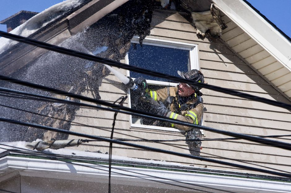 A fire fighter from Co. 2 leans out an attic window to spray water onto the roof overhang of a house at 29 North First Street during a fire in Meriden, Wednesday morning, Mar 4, 2009. A live power line connected to the house fell during the fire onto the porch roof forcing fighters to reach the fire from the window area while avoiding the hazard of the power line.