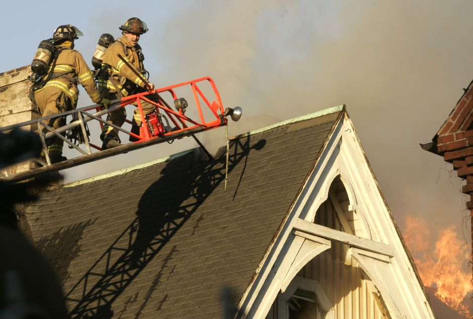 Meriden firefighters work to vent the roof of a house at 91 Lincoln Street which caught fire shortly after 6 p.m. Tuesday March 20, 2007. (dave zajac)