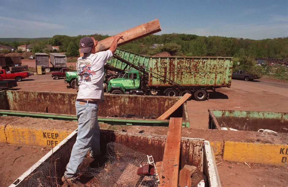 Rj file photo - Phil Oranski tosses a piece of lumber into a container at Southington