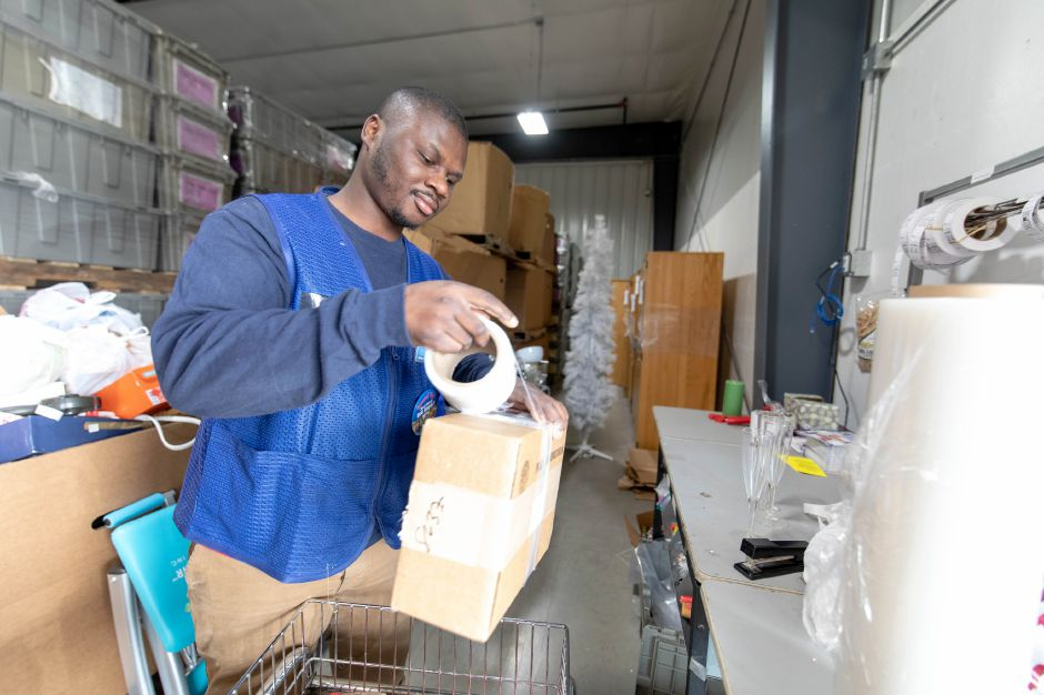Kwadwo Osei wraps a box in the back of the Goodwill store at 349 New Britain Ave during its first day in business on Nov. 8, 2018. | Devin Leith-Yessian/Plainville Citizen