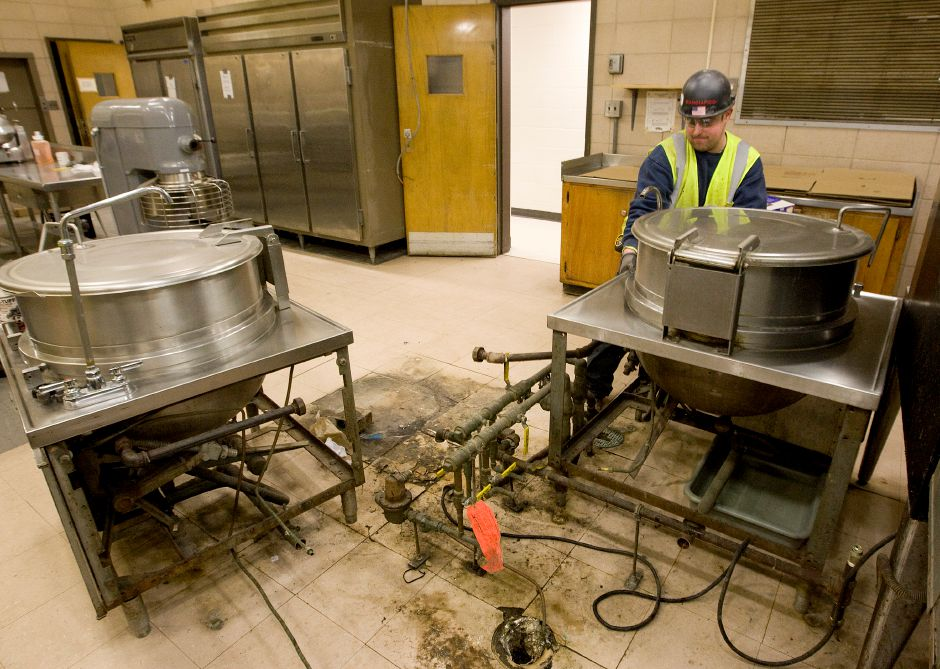 A worker removes equipment from the kitchen at Maloney High School in Meriden, Friday, March 27, 2015. A temporary cafeteria in the school