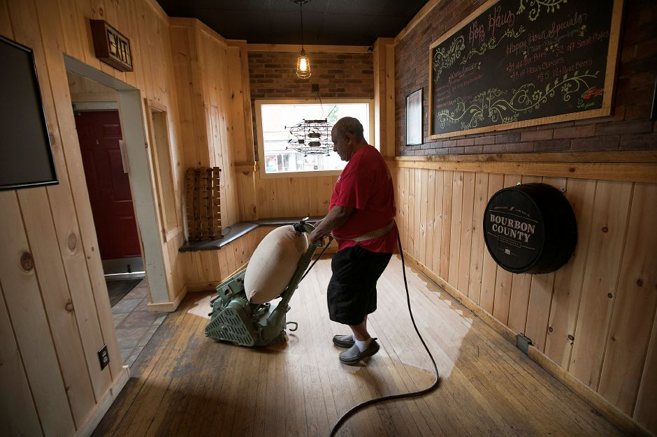 FILE PHOTO: A worker for Meriden based Allstate Floor Coverings refinishes the floor at Hop Haus in Southington Monday, Sept. 18, 2017 after a vehicle crashed into the business Sunday morning. | Dave Zajac, Record-Journal