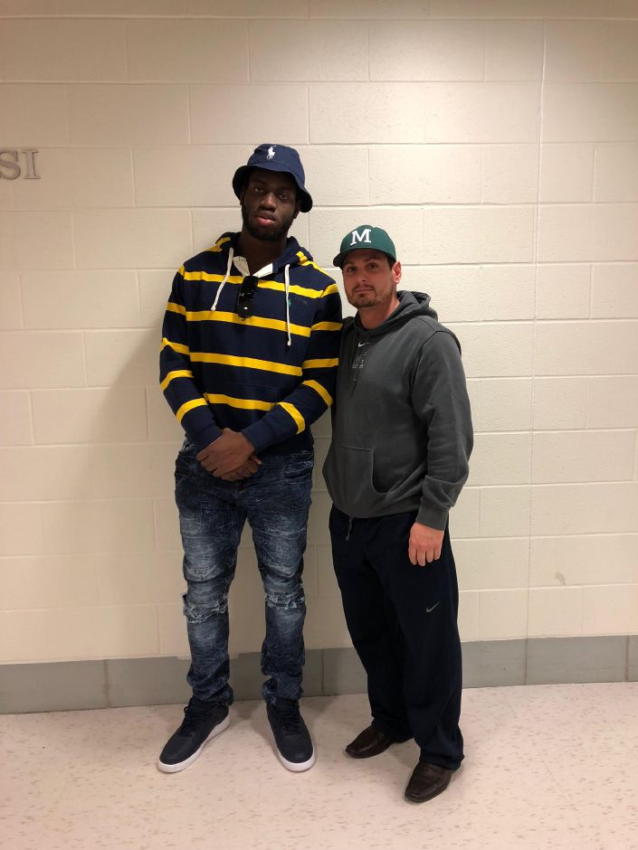 James Ubaike, who signed with DI Eastern Illinois earlier this year, poses with Maloney High School football coach Kevin Frederick.