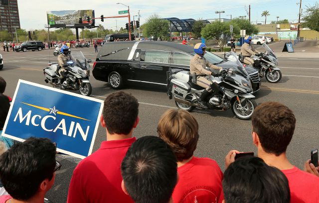 People line the street as the hearse carrying Sen. John McCain, R-Ariz., makes it