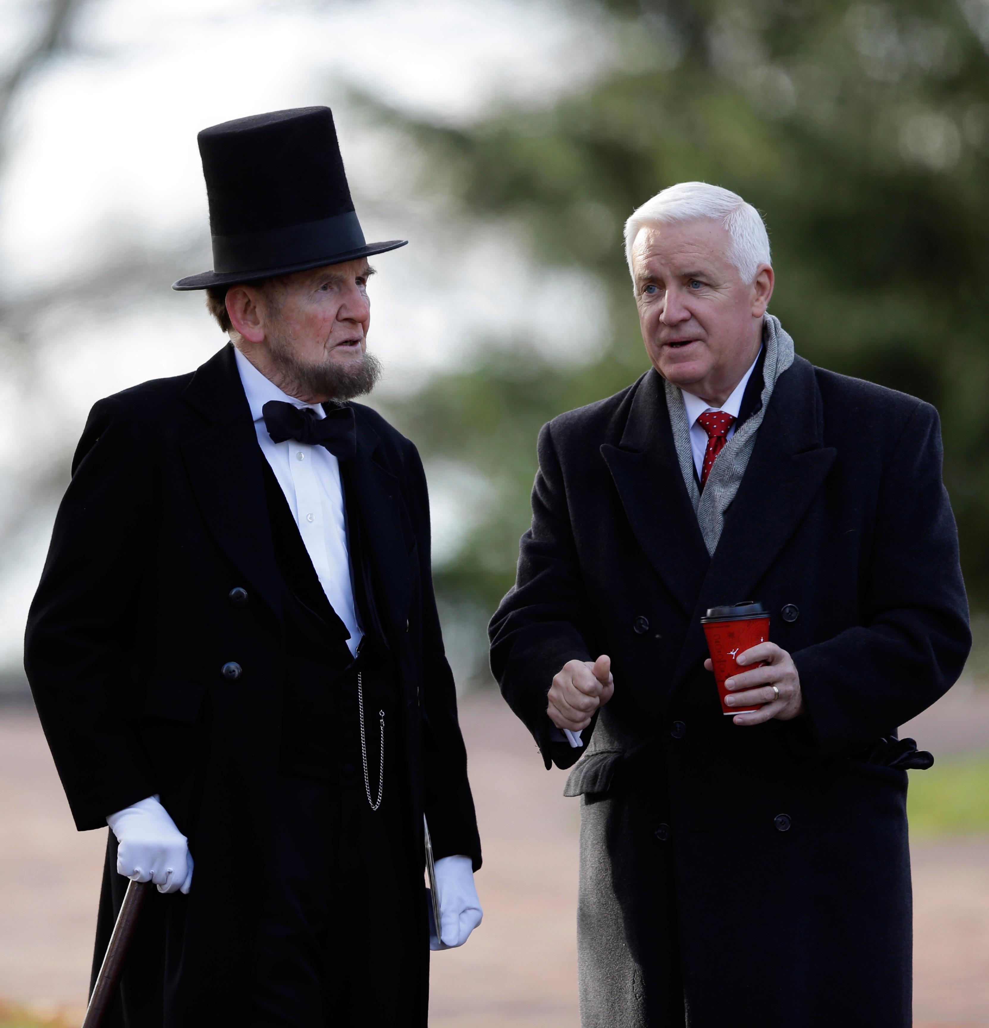 Pennsylvania Gov. Tom Corbett, right, speaks with James Getty, portraying President Abraham Lincoln, before a ceremony commemorating the 150th anniversary of the dedication of the Soldiers National Cemetery and President Abraham Lincoln