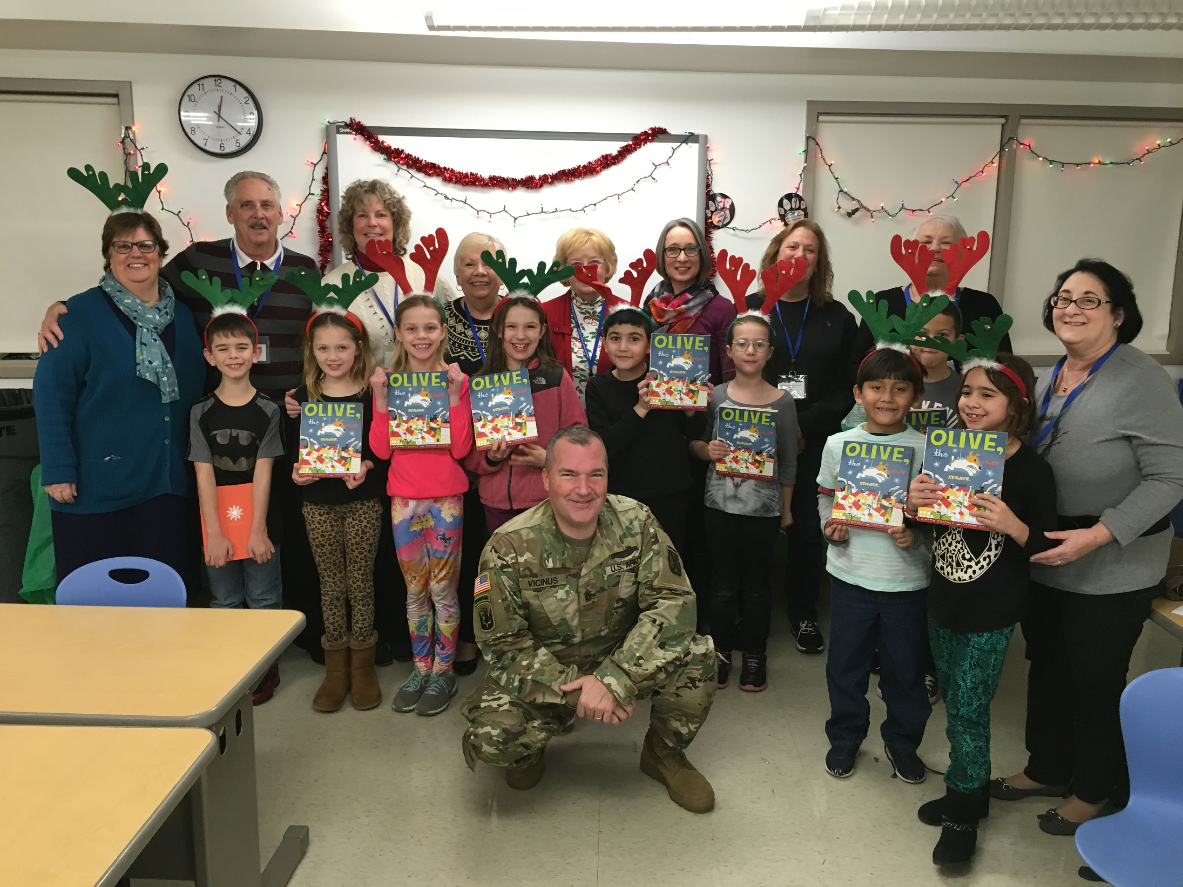 As part of its Community Outreach Program, Plainville's VFW Post 574 donated books to the Plainville Community Schools Reading Partners Program, which is in all three elementary schools. Pictured: Reading Partners Program participants at Louis Toffolon Elementary School pose with Principal Lynn Logoyke and their book donations presented by Command Sergeant Major Paul Vicinus, front.