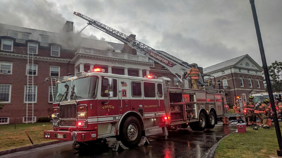 Firefighters use a ladder truck to battle a blaze caused by a lightning strike at Choate Rosemary Hall in Wallingford on Monday. Michael Gagne, Record-Journal staff