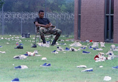 A rescue team member sits in a chair surrounded by shoes of Cuban inmates who were holding hostages at the Talladega Federal Correctional Institution, Aug. 30, 1991. Rescue teams stormed the facility early Friday morning. Officials made the inmates strip in the yard by the Alpha Complex which they had controlled for nine days. (AP Photo/Dave Martin)