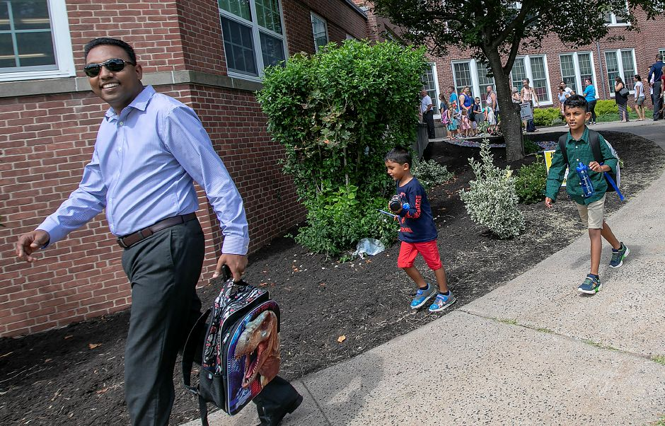 Santosh Sanganalmath smiles while picking up children Akshar, 4, center, and Eashan, 7, during early dismissal on the first day of school at Derynoski Elementary School in Southington, Thursday, August 30, 2018. Dave Zajac, Record-Journal