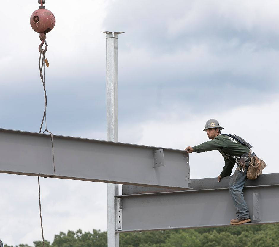 A worker helps guide a beam in place as work continues on a new development that will feature an Aldi store, Chipotle Mexican Grill and Chick-fil-A on Queen Street in Southington, Monday, August 14, 2017. | Dave Zajac, Record-Journal