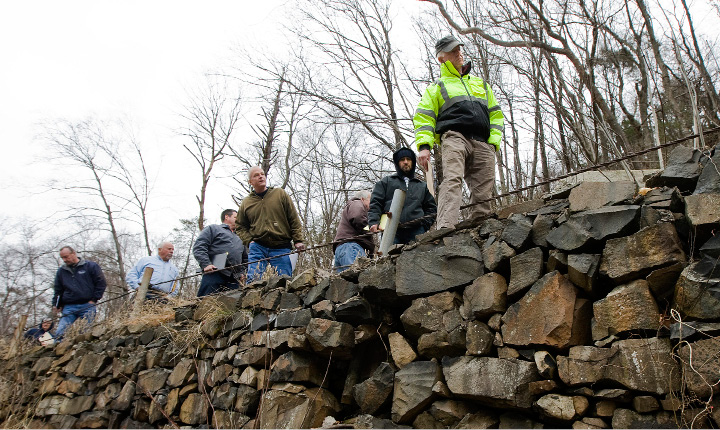 Contractors look over a rock wall in need of repair along the Merimere Reservoir in Meriden, Friday, January 20, 2017. A city-funded project to replace a 50-foot section of the stone wall will cost $70,000 and is expected to be completed in early spring.  | Dave Zajac, Record-Journal