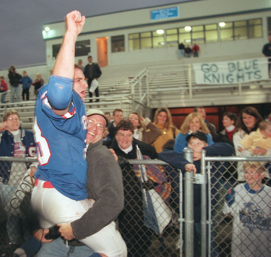 RJ file photo - Jonathan Wholley gets a victory lift from his father, John, Dec. 5, 1998.