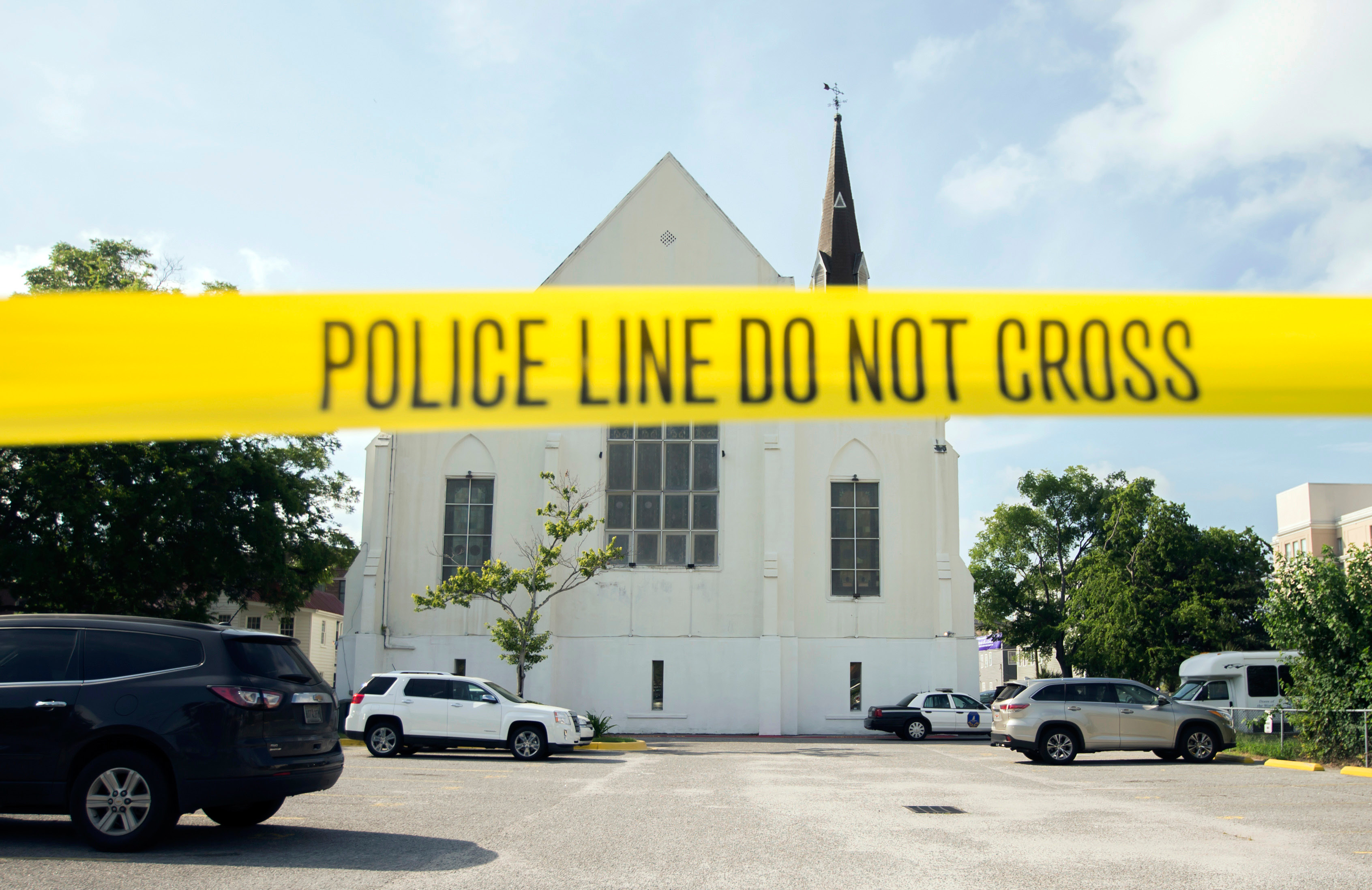 FILE - In this June 19, 2015 file photo, police tape surrounds the parking lot behind the AME Emanuel Church as FBI forensic experts work the crime scene, in Charleston, S.C. Prosecutors who wanted to show that Dylann Roof was a cruel, angry racist simply used his own words at his death penalty trial on charges he killed nine black people in June 2015 at a Charleston church. Roof