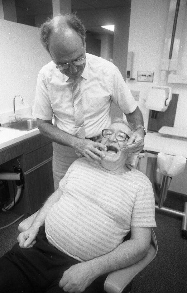 RJ file photo - George Stanley, seated, gets low-cost professional treatment from his dentist, Dr. Robert Bailey o fMeriden, July 1989.