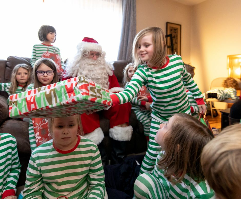 Children open presents at the Keane household on Woodhaven Drive during the Kensington Fire-Rescue Santa