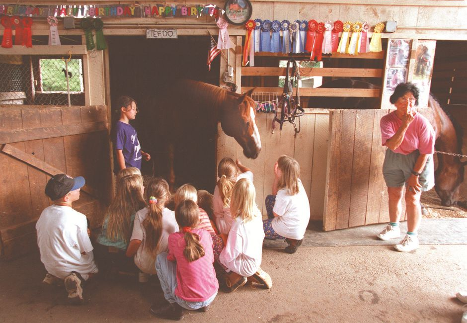 RJ file photo - Rap-A-Pony owner Rita Rapuano, right, explains the muzzle markings on Teedo, one of her horses, during a birthday party at her stables. Standing next to Teedo is Brittany Celata, 10, of Meriden, a volunteer at the stables, August 1998.