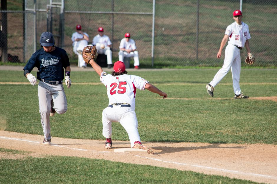 Wallingford first baseman Russell Edeen reaches out for the ball, which would ultimately miss and hit Branford